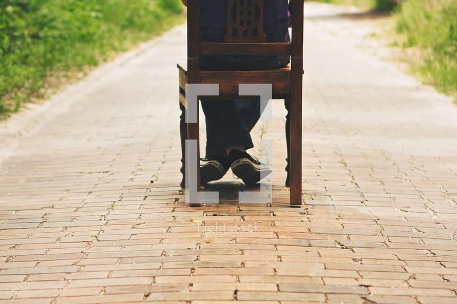 A person sitting on a chair on a brick sidewalk.