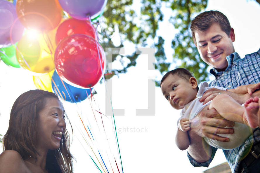 mother holding balloon and father holding a baby