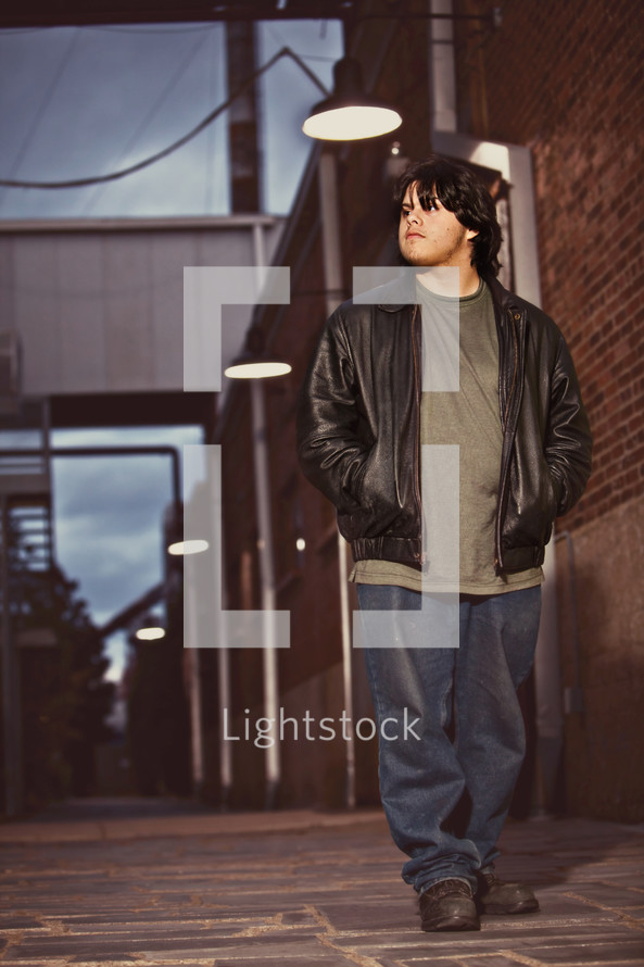 young man walking down street - dusk