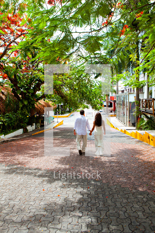 A couple holding hands walking down the street
