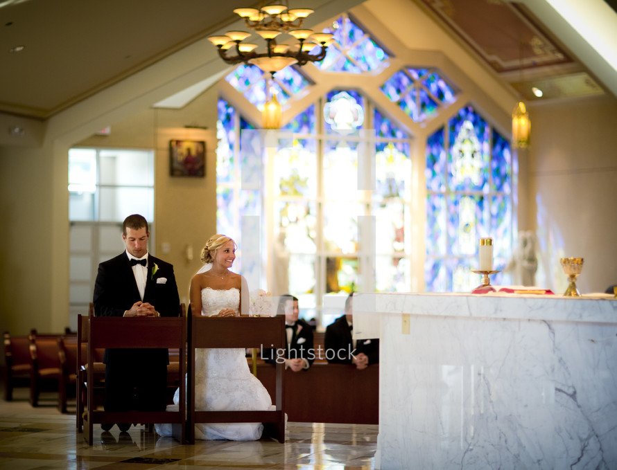 bride and groom kneeling in prayer at an altar during rehearsal