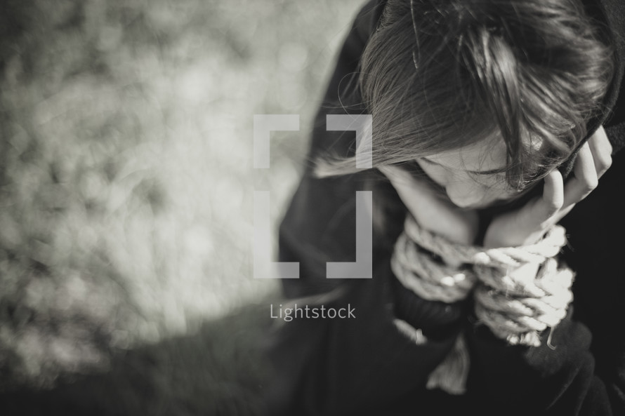 Child with hands tied in ropes