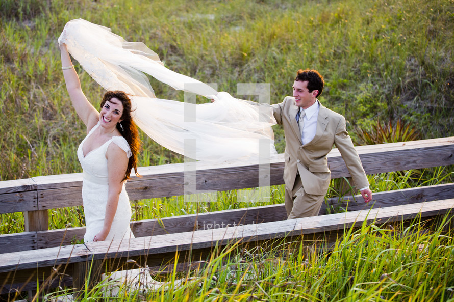 bride walking holding her veil and groom following