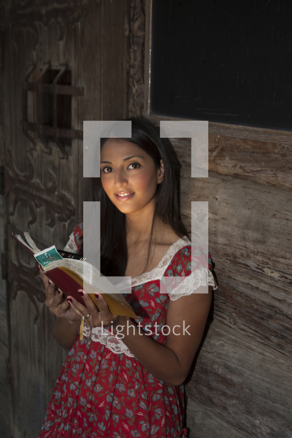 woman with glowing face reading a Bible