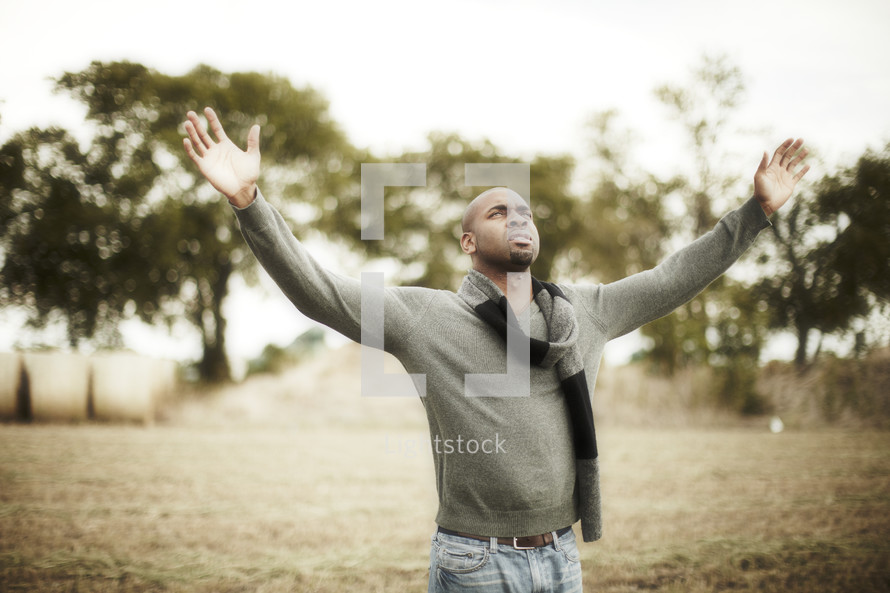man with his arms raised in worship to God