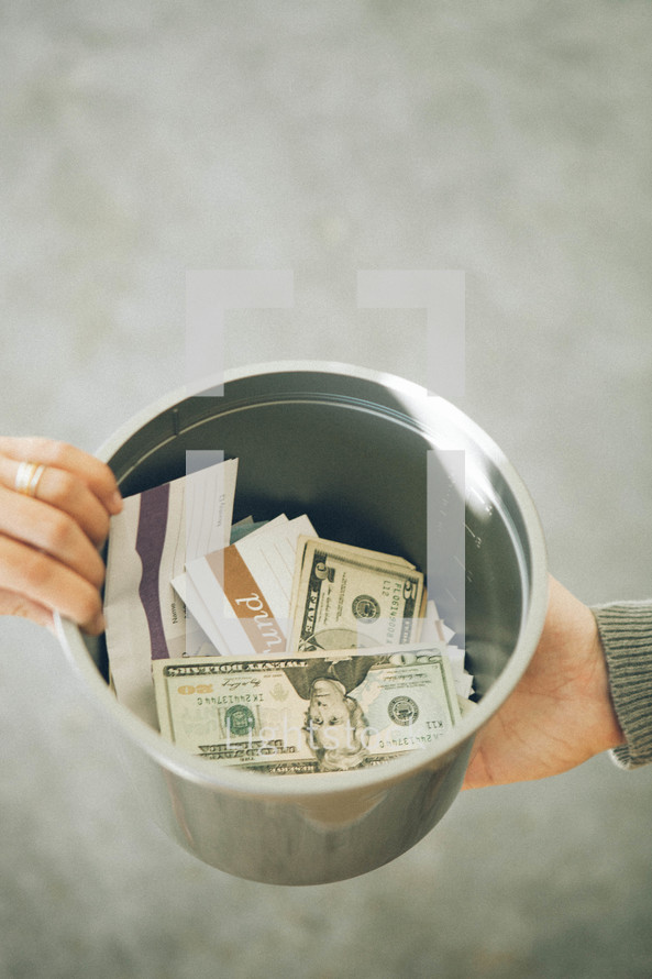 Offering bucket being passed with money and checks inside