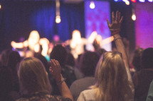 worshipers with raised hands at a worship service