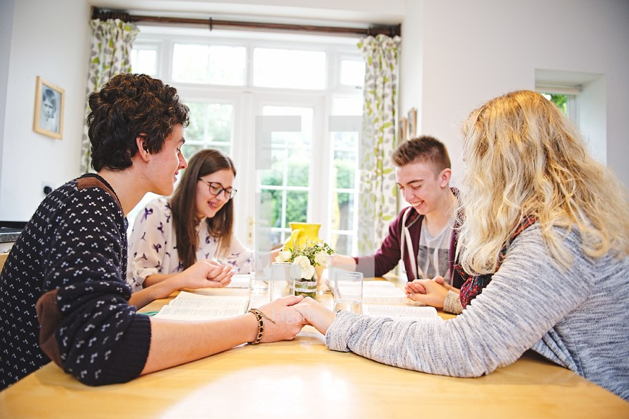 teens holding hands in prayer at a Bible study
