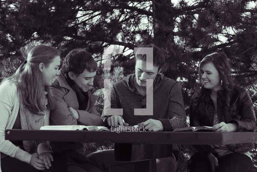 college students reading their Bibles outdoors at a picnic table during a Bible study