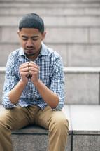 man sitting with praying hands
