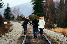 Three people walk along a railroad track.