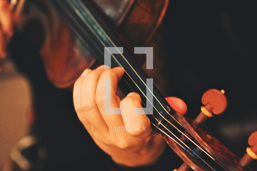 Hnd holding neck of violin.