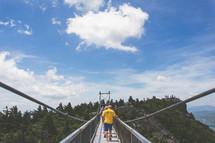 people walking across a swinging bridge