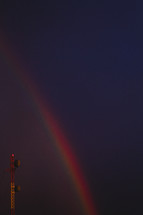 A communications tower is juxtaposed with a rainbow on a dark sky.