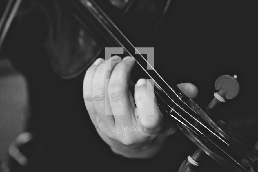 Hand holding neck of violin.