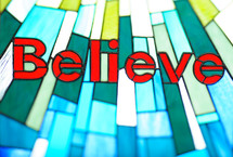 word Believe in a stained glass window