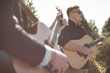 musicians playing guitars outdoors
