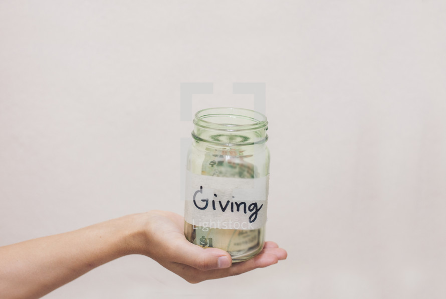 hand holding out a giving jar