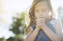 Little girl in prayer outside with sun shining.