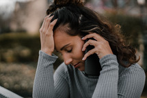a young woman receiving bad news during a phone conversation
