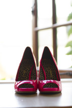 Hot pink high heels on a window sill.