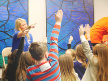 a teacher and students raising their hands