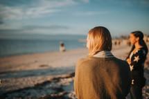 women in sweaters standing on a beach