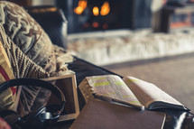 open Bible, headphones, tablet, and journal on a coach in front of a fire place
