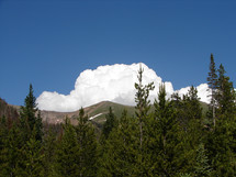 Clouds behind mountain range and trees.