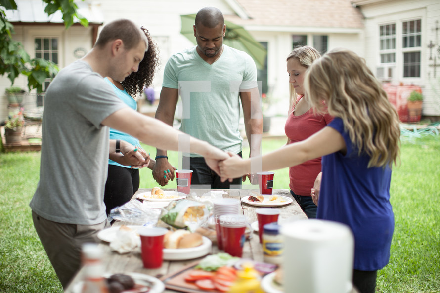 friends holding hands in prayer over an outdoor table before eating