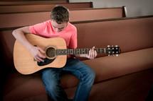 Teen boy playing guitar sitting on a pew