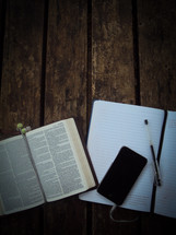 open Bible, notebook, pen, earbuds, and iPhone