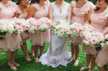 torsos of bride and bridesmaids holding bouquets