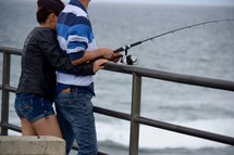 a couple snuggle and fishing on a pier