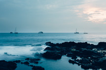 sail boats and a rocky shore