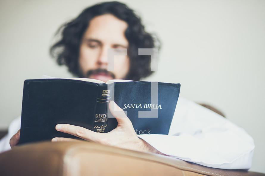 a man reading the Santa Biblia