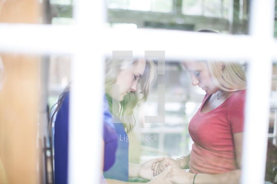 women holding hands in prayer through a window