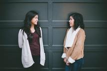 Two girls standing in front of a garage door.