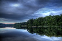 clouds and trees reflecting on lake water