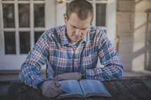 A young man sitting at a table reading the Bible