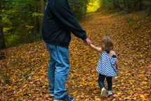 a father and toddler daughter walking holding hands through a fall forest