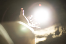 a hand reaching towards glowing light