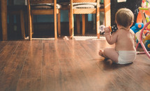 a baby in diapers sitting on a wood floor