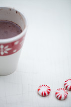 A cup of hot chocolate in a Christmas cup and peppermint candies on a white table.