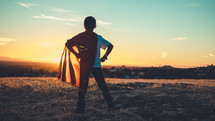Boy facing the sun, wearing a superman cape, looking determined.
