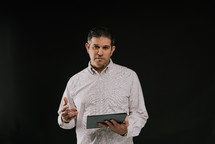 a man holding a tablet speaking