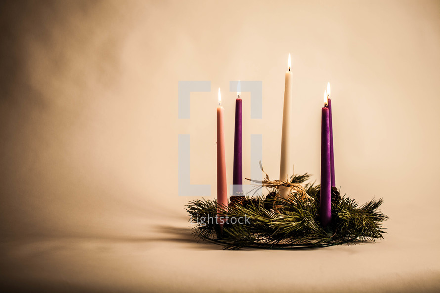 Five lit candles in pine wreath.