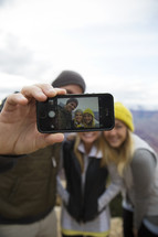 friends taking a selfie on a mountaintop