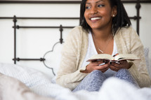 young woman sitting in bed reading a book