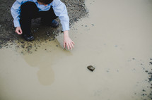 boy playing in a puddle